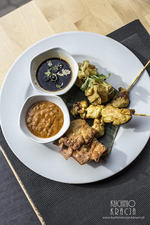 Talerz z przekąskami na ciepło - chrupiące pierożki wonton, grillowane mini szaszłyki z piersi kurczaka, pierożki Dim Sum gotowane na parze z nadzieniem z kurczaka i krewetek. Podawany z dwoma sosami - orzechowym z curry i sojowo-imbirowym, Restauracja Basil & Lime